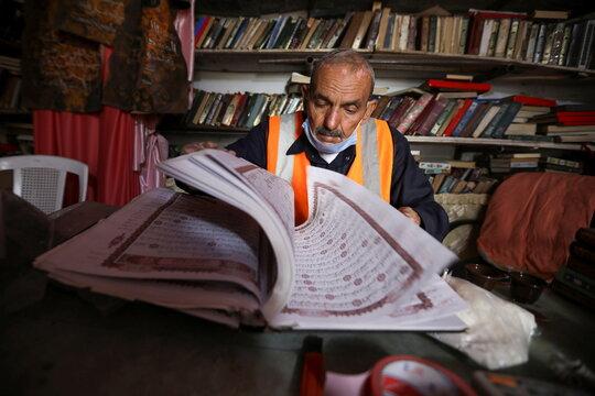 Mohammad Salem Abu Zakrya checks a copy of the Koran at his library in Jerash