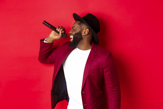 Passionate black male singer performing against red background, singing into microphone, wearing party outfit, standing over red background