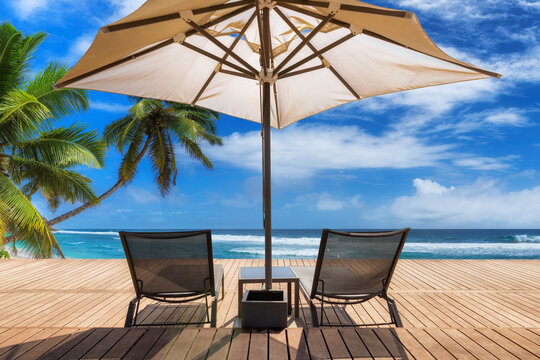 Sunny beach with umbrella and deckchairs on wooden floor, palm trees and the turquoise sea on Tropical island.