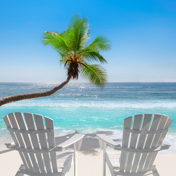 Sunny beach with beach chairs on white sand, tropical sea and coco palms. in Caribbean island.