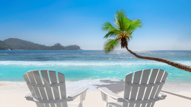 Sunny beach with beach chairs on white sand, tropical sea and coco palms. Summer vacation and tropical beach concept.