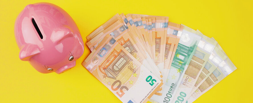 top view of stack of euro bills and piggy bank on yellow background, saving money and finance concept