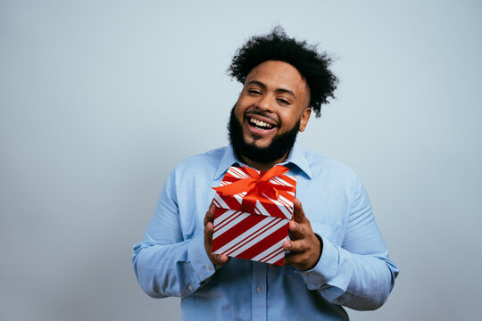 Portrait of a very happy young man smiling and holding red Christmas gift box present.