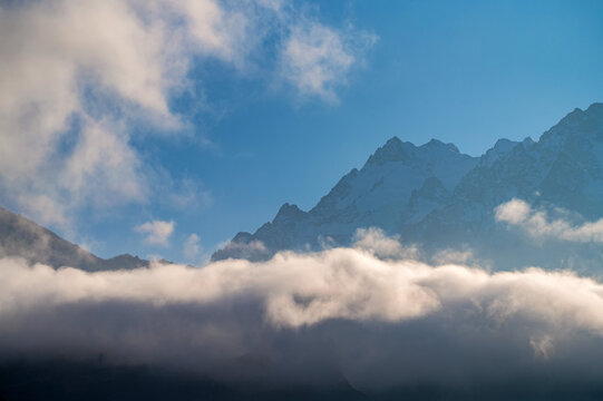 Rocks behind clouds in North Caucasus mountains in autumn on sunny day
