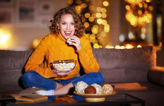 young  delighted cheerful woman with popcorn laughs and watches  christmas movie on  TV   at home in evening  alone