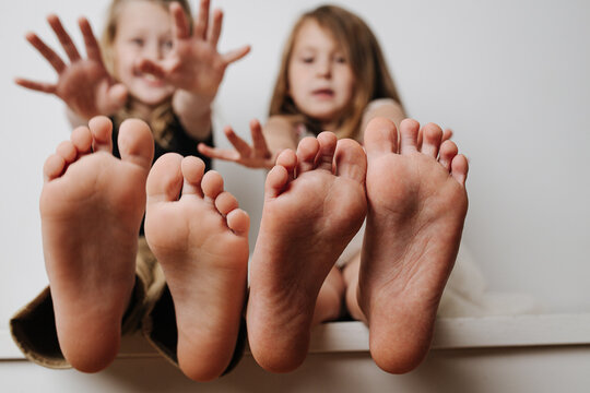 Brother and sister holding bare feet close up to the camera. Their blurred faces in a background. Hands reaching to camera.