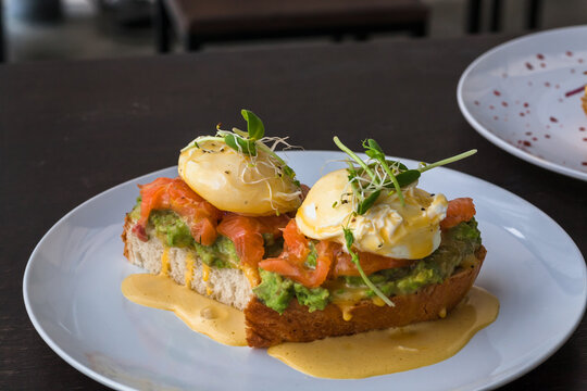 Restaurant food and some plates of breakfast toasts with salmon, guacamole, poached egg, with sauce. Fresh food close-up
