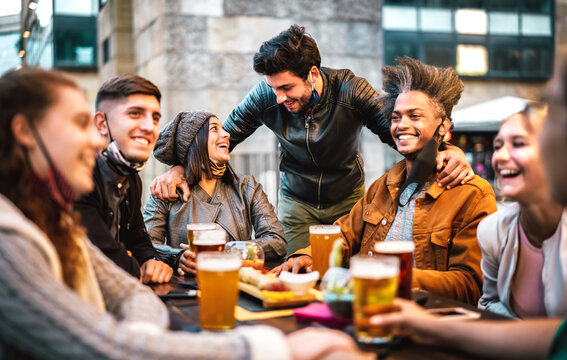 Young people drinking beer with open face mask - New normal lifestyle concept with milenial having fun together talking on happy hour at outside brewery bar - Warm filter with focus on central people