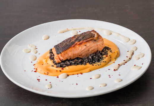 Plate with salmon fish fillet, sweet potato puree, quinoa and creamy sauce. Fresh food close-up