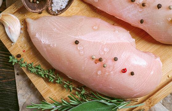fresh raw farm chicken fillet on a cutting board.