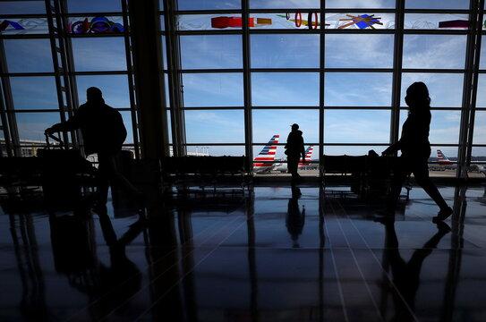 People walk at Reagan National Airport ahead of the Thanksgiving holiday in Arlington
