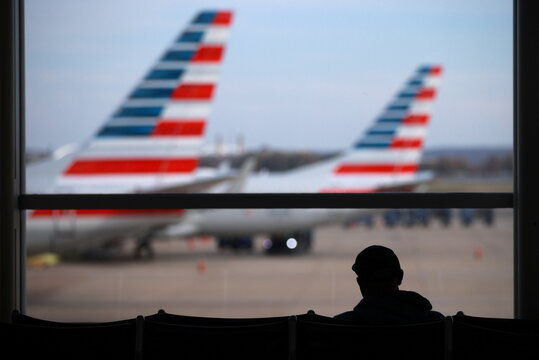 A person sits at Reagan National Airport ahead of the Thanksgiving holiday in Arlington