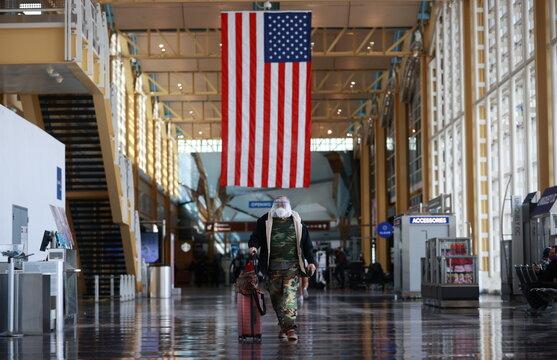 A man walks at Reagan National Airport ahead of the Thanksgiving holiday in Arlington