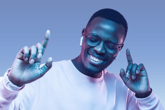 Portrait of happy young african man listening to music with wireless earphones isolated on blue background