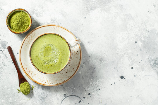 Matcha green tea latte in a cup with cream on a light concrete background. Top view with copy space