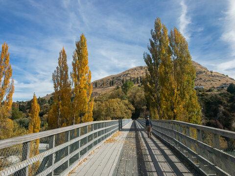 Biker walking on The Lower Shotover Bridge, Queenstown Area, South Island, New Zealand