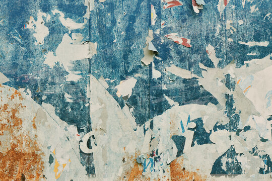 Torn poster paper surface as abstract grunge background, worn damaged printed billboard advertisement