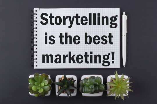 Text Storytelling is the best marketing! Notepad, pen, houseplants on a dark wooden table. Business concept.