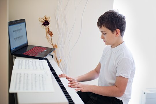 12 years old boy playing the white piano with sheet music.
