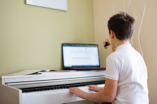 A young boy plays the digital piano with sheet music from his laptop.