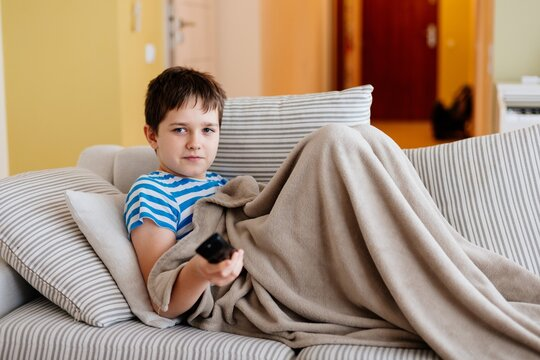A young boy sits on the sofa under the blanket and switches the channels on television.