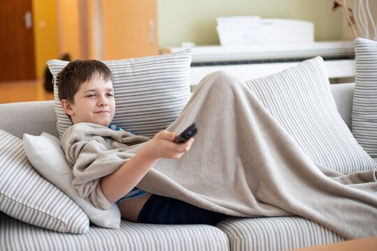 Cute kid is watching TV is lying under a blanket on the sofa with the TV remote in hand.