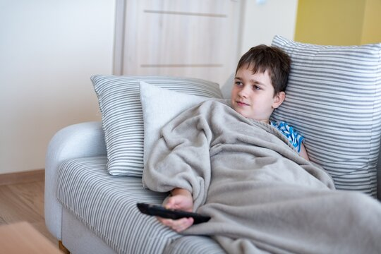 A young boy is lying on the sofa under a blanket, with the remote control in his hand, watching TV.