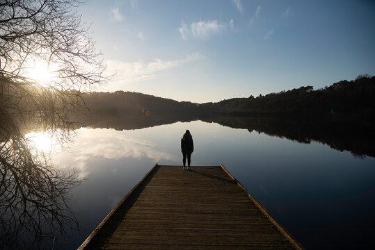 Persona mirando un lago de Mouriscot al atardecer