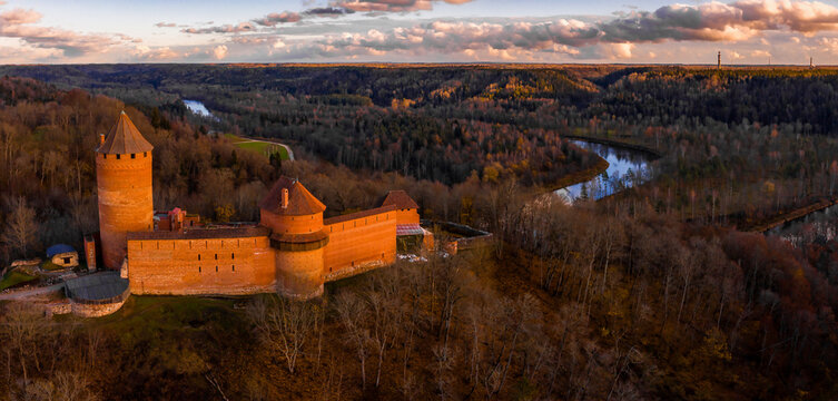 Aaerial view to the Turaida castle and river Gauja at sunset in Sigulda, Latvia. Golden autumn with orange forest and river by the castle.