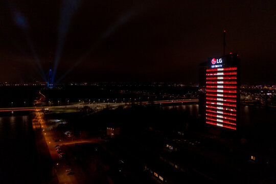"Riga, Latvia, November 18,2020. Light festival ""Staro Riga"". Latvian TV tower and building glowing in Latvian flag lights creating a festive atmosphere. Modern architecture in vivid lights."