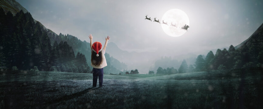 little girl surprised to see Santa Claus on beautiful Christmas night under moonlight in mountains