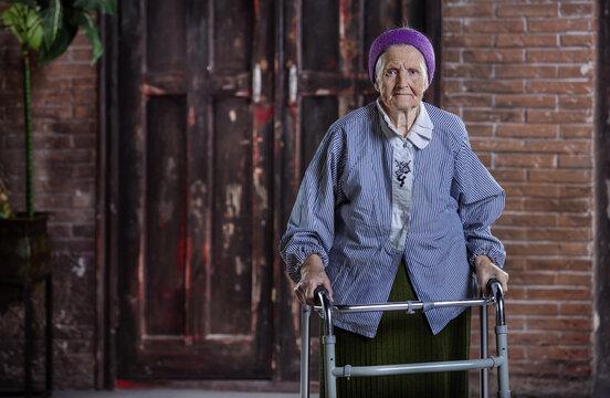 Portrait of senior woman with walker indoors