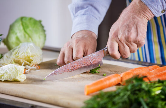 Cropped view of mature man chopping fresh vegetables for salad. Closeup of male hands.
