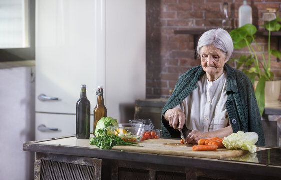 Senior woman chopping fresh vegetables for salad