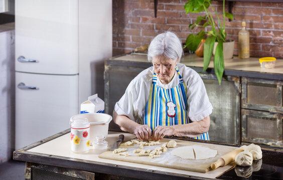 Senior woman preparing pastries in kitchen at home