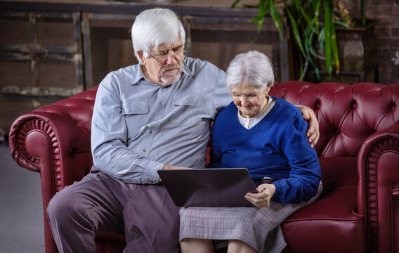Mature man and senior woman using laptop while sitting on couch
