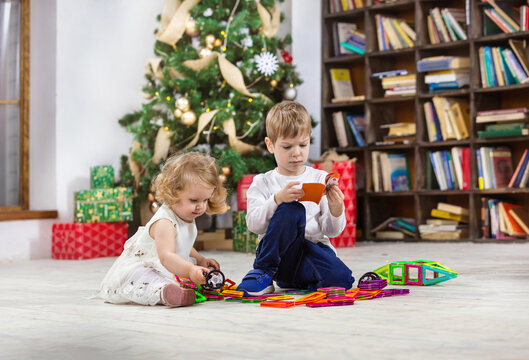 Young girl and boy playing with magnetic toys beside Christmas tree