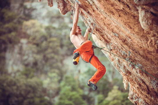 Young rock climber after jumping and gripping small handholds on overhanging cliff