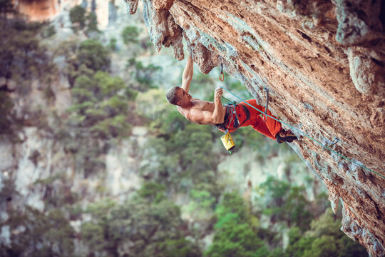 Rock climber clipping rope while climbing challenging route on cliff