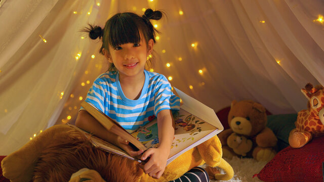 portrait of asian kid playing in tent in living room reading fairy tale