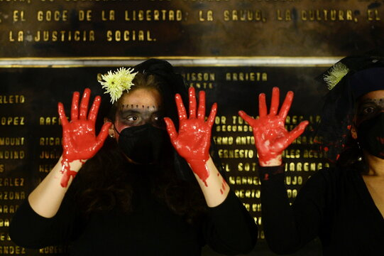 Women show their hands painted in red during a protest to mark the International Day for the Elimination of Violence against Women, in San Salvador