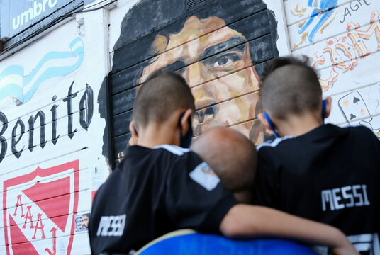 Fans gather to mourn the death of soccer legend Diego Maradona, outside the Diego Armando Maradona stadium, in Buenos Aires