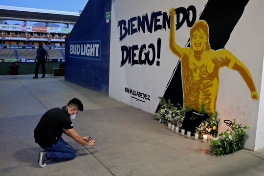 A fan takes a photo of a mural showing late Argentine soccer legend Maradona at the Dorados stadium in Culiacan