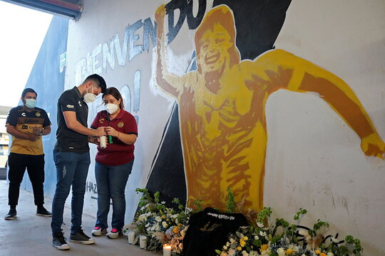 People light up a votive candle next to a mural showing late Argentine soccer legend Maradona at the Dorados stadium in Culiacan
