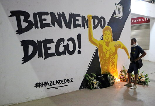 A man stands next to a mural showing late Argentine soccer legend Maradona at the Dorados stadium in Culiacan