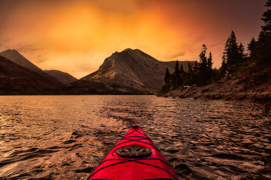 Kayaking in Glacier Lake surrounded by the beautiful Canadian Rocky Mountains during a cloudy summer sunset. Taken in Upper Waterton Lake, Alberta, Canada.