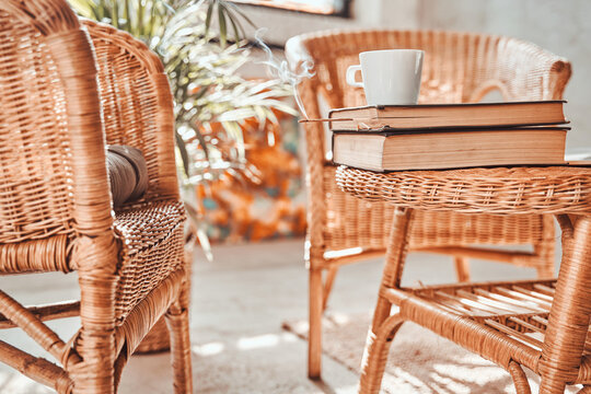 Comfortable living room for solitude and relaxation in daytime with bamboo chairs and table with books and coffee cup on it.