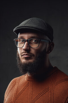 Portrait of adult stylish guy with glasses and black beard posing in dark background.