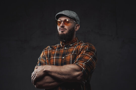 Dressed in checkered shirt with cap and weared with sunglasses bearded hipster guy poses in dark background with crossed arms.