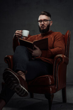 Smart and at the same time stylish man with beard and glasses sits on chair holding coffee cup and book in dark background.